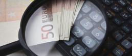 calcolarice con una lente di ingrandimento e delle banconote